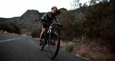 vorderer niedriger Winkelschuss des Radfahrers, der entlang der Bergstraße läuft