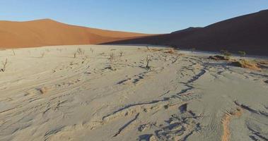 4k Luftaufnahme eines männlichen Touristen, der über totes Vlei in der Namib-Wüste innerhalb des Namib-Naukluft-Nationalparks geht