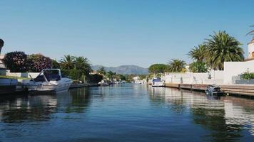 pov video voile sur un bateau à travers le canal avec l'immobilier d'élite. empuriabrava, espagne, catalogne. en arrière-plan, des montagnes visibles