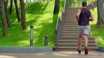 uomo fitness correre su per le scale al rallentatore. giovane uomo che corre al piano di sopra