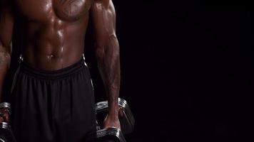 hombre negro musculoso sosteniendo pesas libres