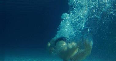fit Mann unter Wasser im Pool schwimmen