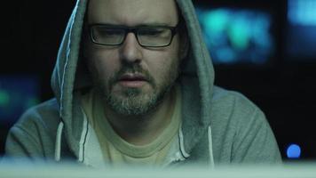 riprese ritratto di un impiegato maschio concentrato che indossa un cappuccio e lavora su un computer in una stanza buia dell'ufficio con schermi con mappe e dati.