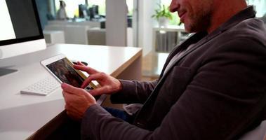 Ejecutivo de negocios atento escribiendo notas en su tableta en la oficina video