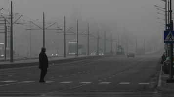 Man crossing wide highway in early misty morning video