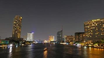 Hermoso lapso de tiempo de la ciudad de Bangkok al anochecer a la noche con barcos iluminados en el río Chao Phraya