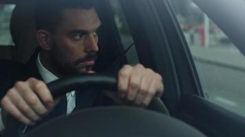 uomo d'affari alla guida di un'auto nel quartiere degli affari, controllando il tempo. video
