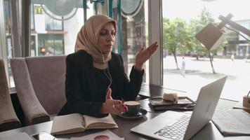 Middle Eastern businesswoman telecommuting from cafe video