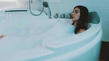 jovem acariciando-se na banheira cheia de espuma. relaxante. satisfação video