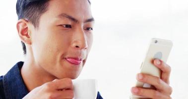 hombre tomando café y usando un teléfono inteligente