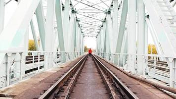 giovane uomo va avanti sul ponte ferroviario