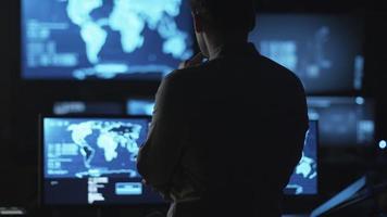 empleado masculino de ti está mirando pantallas de computadora con mapas y datos en exhibición en una habitación oscura de la oficina. video