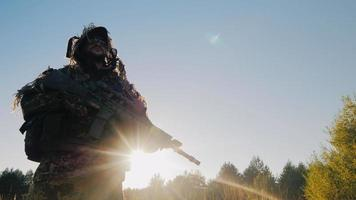 The soldier in the American ammunition worth against the sky. The sun shines on his arms. Lower angle shooting
