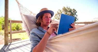 Teen reading on his digital tablet relaxing in a hammock