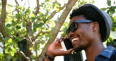 retrato de jovem hippie sorrindo e falando ao telefone video