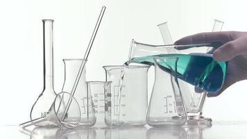 verter líquido azul en un vaso de precipitados con un erlenmeyer video