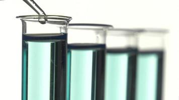 tubo de ensayo lleno de líquido azul, vertiendo una gota de agua
