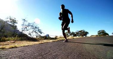 African american runner along a mountain road with morning sun flaring