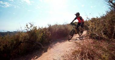 Mountainbiker, der bergab auf einem Feldweg fährt