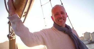 bell'uomo maturo su yacht nel pittoresco tramonto video