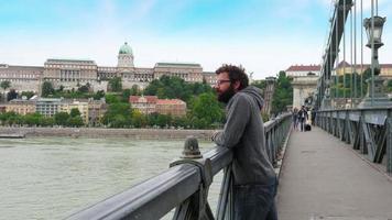 um único homem olhando para a vista do castelo de Budapeste, ponte de corrente video
