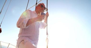 uomo anziano su uno yacht con caffè guardando l'orizzonte