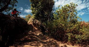 Extremer Mountainbiker, der kurz davor ist, steil bergab zu fahren