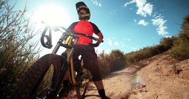 stolzer Mountainbiker, der mit seinem Fahrrad auf Feldweg steht