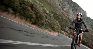 Foto frontal de um ciclista correndo ao longo da estrada na montanha video