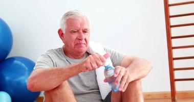 homem sênior bebendo água sentado no chão