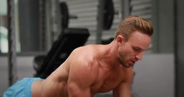 Mann macht Hantelreihen im Fitnessstudio