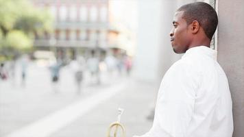 Black man plays a trumpet in the street and then smiles at the camera video
