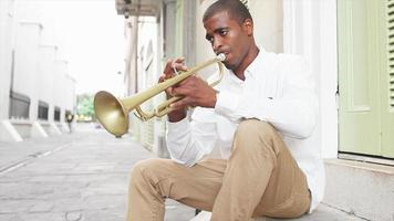 Black man plays a trumpet in the street and then gets a text message video