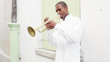 homme noir sourit à la caméra et joue de la trompette dans la rue video