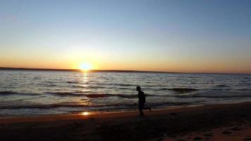 ragazzo adolescente corre lungo la riva di un grande lago. corre lungo il bordo dell'acqua.