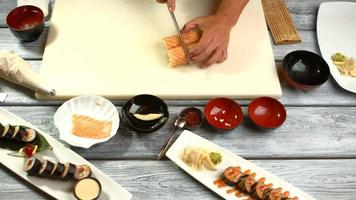 Hand with knife cutting sushi.