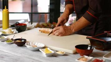 Hands cutting sushi with knife.