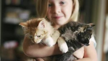 A little girl smiling and holding two kittens in her arms