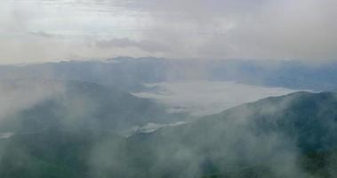 Wolke und Nebel am Morgen über Berg und kleinem Dorf