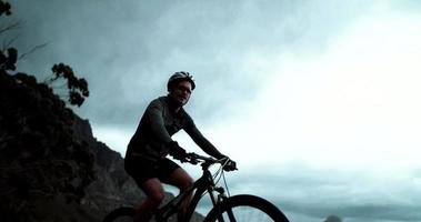 Disparo hacia arriba de ciclista en persecución con bicicleta en carretera de montaña video