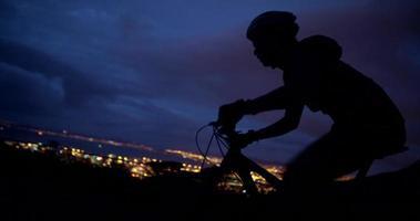 foto para cima de ciclista em perseguição com bicicleta na estrada da montanha video