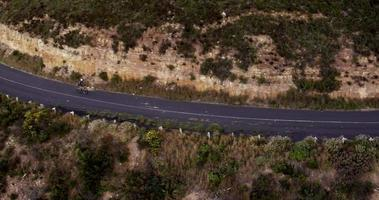 Flying drone shot of cyclist riding along mountain road