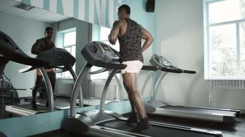 Mann läuft auf Laufband in der Turnhalle
