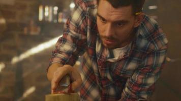 jovem está trabalhando com madeira em uma garagem em casa. video