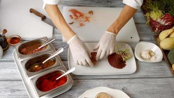le mani mettono la carne sul piatto.