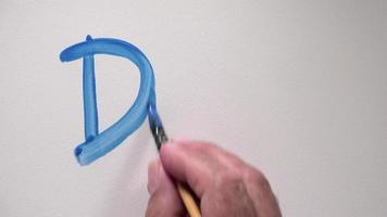 """Mano humana escribiendo la palabra """"dibujar"""" con gouache azul"""