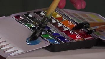 pincel tomando aquarela na paleta