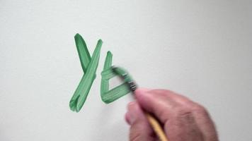 """Mano humana escribiendo la palabra """"sí"""" con gouache verde"""