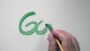 """mão humana escrevendo a palavra """"gol"""" com guache verde"""