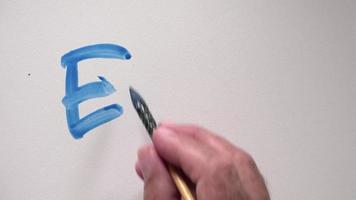"mano umana che scrive parola ""e = mc2"" con tempera blu video"